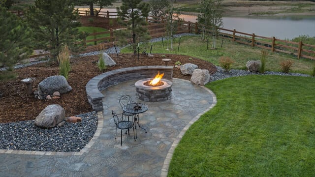 An outdoor firepit surrounded by a patio area and rock and pine mulch. Landscaping boulder add an accent to the landscaping.